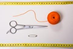 Fondo para el hilo, la cinta métrica y las tijeras anaranjados del sastre Fotos de archivo