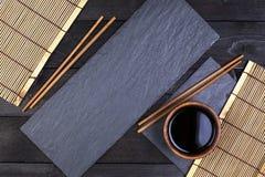 Fondo para el sushi Estera de bambú, salsa de soja, palillos en la tabla oscura Fotografía de archivo