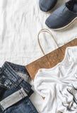 Fondo para mujer de las compras de la ropa Vaqueros, zapatillas de deporte, camiseta, bufanda y una bolsa de papel en un fondo li Foto de archivo