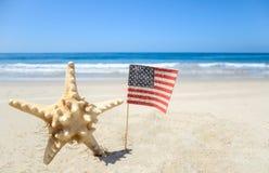 Fondo patriótico de los E.E.U.U. con las estrellas de mar en la playa arenosa Imagenes de archivo