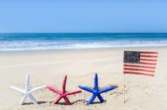 Fondo patriótico de los E.E.U.U. con las estrellas de mar en la playa arenosa Imagen de archivo
