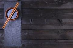 Fondo per i sushi Salsa di soia, bastoncini sulla tavola nera Vista superiore con lo spazio della copia Fotografia Stock