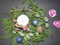 Fondo por la Navidad y el Año Nuevo Rama spruce verde con una bola de la Navidad en un fondo negro vela blanca con christma Fotografía de archivo