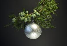 Fondo por la Navidad y el Año Nuevo Rama spruce verde con una bola de la Navidad en un fondo negro vela blanca con christma Foto de archivo libre de regalías