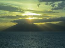 Fondo Puesta del sol Mar y monta?as Los rayos del ` s del sol hacen su manera a trav?s de las nubes foto de archivo libre de regalías