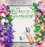 Fondo que cultiva un huerto floral con el surtido de flores coloridas del jardín, de cuaderno de papel, de herramientas que culti Imágenes de archivo libres de regalías