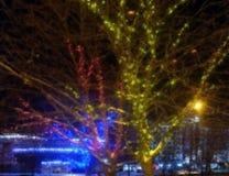 Fondo que empa?a Ciudad de la noche Árbol entrelazado con las guirnaldas coloridas imágenes de archivo libres de regalías