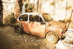 Fondo quebrado concreto del ladrillo del viejo del vintage de Fiat viejo del coche del marrón tono clásico de la sepia intemporal fotografía de archivo libre de regalías