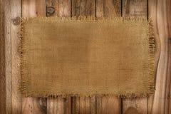 Fondo rústico del material de la arpillera en una tabla de madera con la copia Fotos de archivo libres de regalías