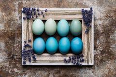 Fondo rústico feliz de Pascua con el espacio de la copia DIY teñió los varios tonos de los huevos de Pascua azules y del marco de Fotografía de archivo