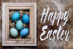 Fondo rústico feliz de Pascua con el espacio de la copia DIY teñió los varios tonos de los huevos de Pascua azules y del marco de Imágenes de archivo libres de regalías