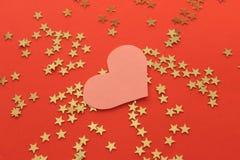 Fondo rojo con las estrellas y el corazón brillantes de oro Foto de archivo
