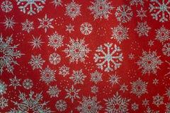 Fondo rojo de la Navidad con los copos de nieve Imagenes de archivo