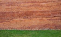 Fondo rojo de la pared del suelo y campo de hierba verde imágenes de archivo libres de regalías