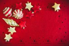Fondo rojo de la tarjeta de Navidad con las decoraciones, bolas y estrellas, y lugar de oro para el texto fotos de archivo