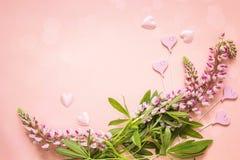 Fondo romántico con las flores del lupine y los corazones decorativos encendido Foto de archivo libre de regalías