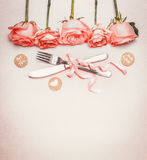 Fondo romántico de la cena con el cubierto de la tabla: las rosas confinan, los cubiertos y cinta en el fondo en colores pastel,  imágenes de archivo libres de regalías