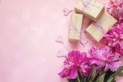 Fondo romantico con le peonie, i contenitori di regalo ed i cuori sul rosa Fotografia Stock