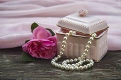 Fondo rosa con le perle del contenitore e della perla di regalo e una rosa, giorno di madre, simboli di amore immagini stock