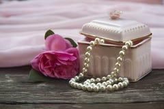 Fondo rosa con le perle della perla e di una scatola immagine stock libera da diritti