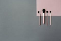 Fondo rosa grigio con le spazzole cosmetiche Fotografia Stock