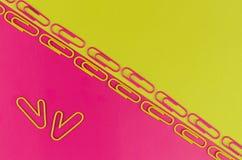 Fondo (rosado-amarillo) bicolor de la oficina con los clips de papel Fotos de archivo