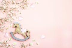 Fondo rosado con el mini flowe del juguete y del gypsophila del caballo mecedora Imagenes de archivo