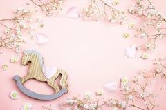 Fondo rosado con el mini flowe del juguete y del gypsophila del caballo mecedora Foto de archivo