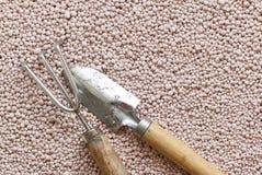 Fondo rosado con las bolas minerales de los fertilizantes Imagen de archivo libre de regalías