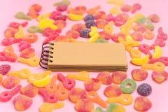 Fondo rosado con las jaleas azucaradas y la libreta en blanco Lugar para su texto imagen de archivo