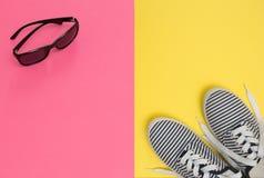 Fondo rosado y amarillo con las gafas de sol y los zapatos rayados, su Fotografía de archivo