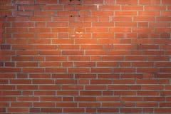 Fondo rosso del muro di mattoni con il punto culminante naturale del sole immagini stock libere da diritti