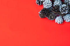 Fondo rosso di Natale con le pigne Immagini Stock