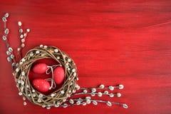 Fondo rosso di pasqua Corona del salice di Pasqua con le uova di Pasqua rosse su fondo rosso Vista superiore, spazio della copia immagine stock libera da diritti