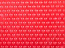 Fondo rosso di plastica con molti punti rotondi del cono Fotografia Stock Libera da Diritti