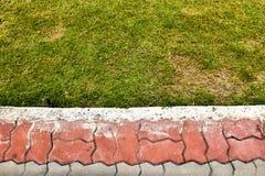 Fondo rosso e grigio dell'erba della pavimentazione Immagini Stock Libere da Diritti