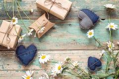 Fondo rurale con le margherite, i cuori decorativi ed i contenitori di regalo Fotografia Stock