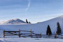 Fondo rurale di inverno con la piccola casa alpina di legno, pini, recinto, campo di neve, montagne, cielo blu Fotografia Stock