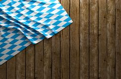 Fondo rustico per Oktoberfest con tessuto bianco e blu bavarese su di legno - rappresentazione 3D Immagini Stock
