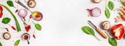 Fondo sano dell'alimento con i vari ingredienti delle verdure, il cucchiaio con olio e lo sbucciatore Fotografia Stock