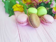 Fondo saporito di legno rosa variopinto di Macaron, foglia del fiore di alstroemeria del biscotto Immagine Stock Libera da Diritti