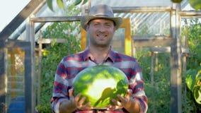 Fondo sonriente de la sandía de Holds Of Ripe del granjero el invernadero en el jardín almacen de video