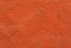 Fondo, struttura: arancia, parete intonacata deliberatamente grezza di un primo piano della costruzione fotografia stock libera da diritti