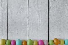 Fondo temático de Pascua o de la primavera de la madera vieja y de los huevos coloreados Imágenes de archivo libres de regalías