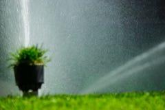 Fondo vago con l'impianto di irrigazione del campo di football americano o di calcio di erba d'innaffiatura automatica Fotografia Stock Libera da Diritti