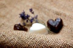 Fondo vago decorativo con l'insieme dei saponi del cuore e dei ramoscelli della lavanda sull'inclinazione della iuta Immagini Stock
