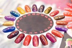 Fondo variopinto differente della tavolozza del manicure della lucidatura di unghie Campioni degli smalti per unghie Chiodo falso fotografie stock