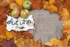 Fondo variopinto e luminoso, foglie di autunno, sul fondo della tela di sacco l'iscrizione è l'autunno su pergamena con gre tre Fotografie Stock