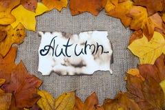Fondo variopinto e luminoso, foglie di autunno, sul fondo della tela di sacco l'iscrizione è l'autunno su pergamena Concetto di a Fotografie Stock