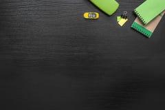 Fondo verde, amarillo, negro del negocio del escritorio de oficina con el post-it, coche, clip de la carpeta, libreta y espectácu Imagen de archivo libre de regalías